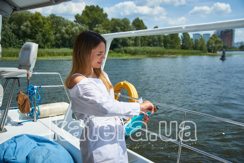 Девушка открывает бутылку шампанского на яхте ЛаВита - katera.ua