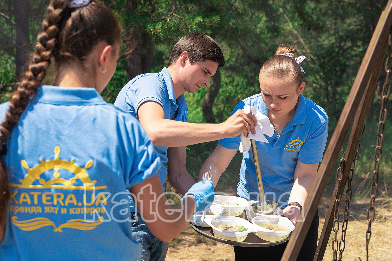 Официанты разливают горячую уху по тарелкам для гостей - katera.ua