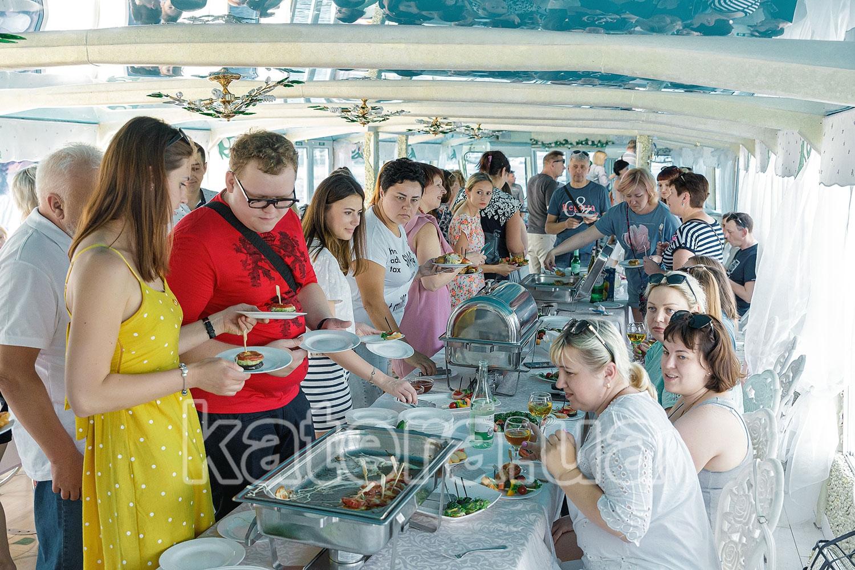 Гости возле фуршетного стола на нижней палубе теплохода - katera.ua