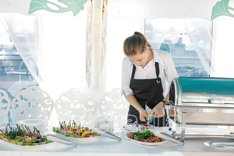 Официант готовит фуршетный стол для гостей - katera.ua