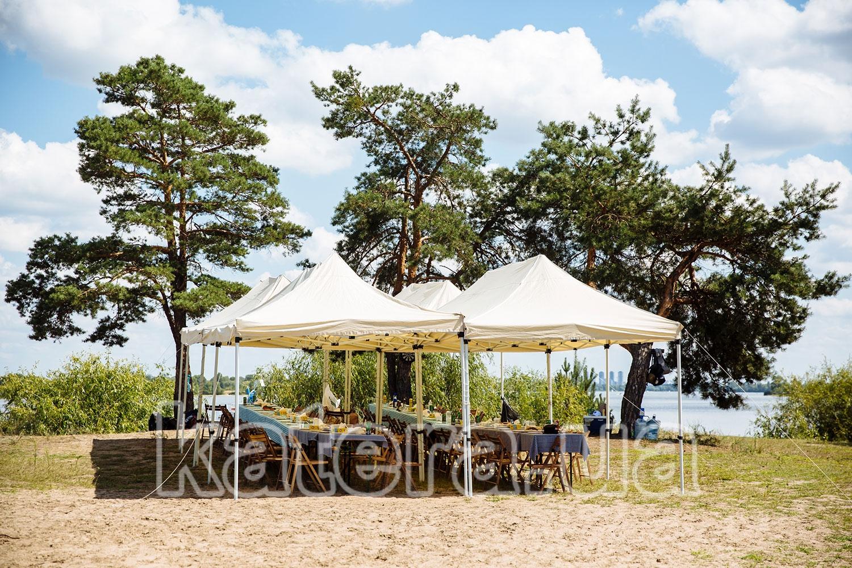 Площадка из тентов, столов и стульев для пикника на острове - katera.ua