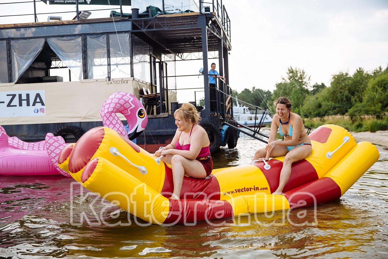 Две женщины весело проводят время на водной надувной качели - katera.ua