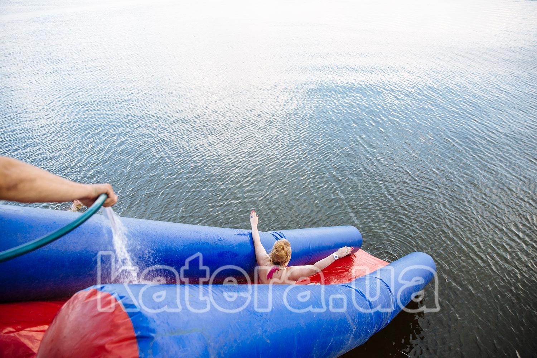 Женщина спускается с надувной горки в воду с верхней палубы - katera.ua