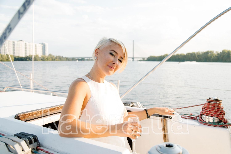 Красивая девушка с бокалом шампанского выходит из салона яхты Пилар - katera.ua