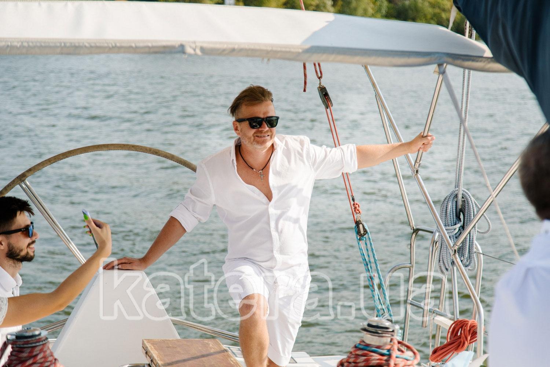 Приятный мужчина в белом на летней площадке яхты Пилар - katera.ua
