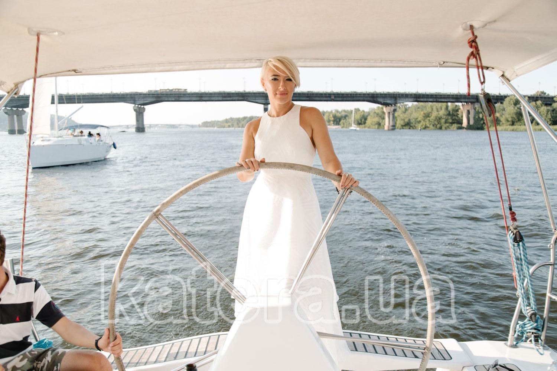Девушка в красивом белом платье за штурвалом яхты Пилар - katera.ua