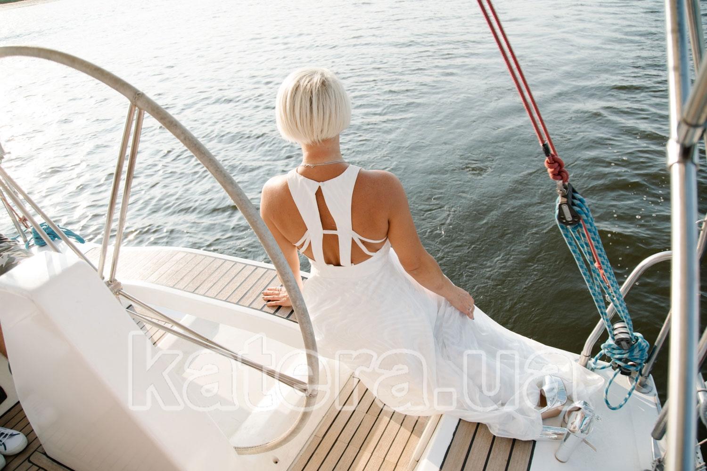 Девушка сидит на корме яхты с деревянным покрытием - katera.ua