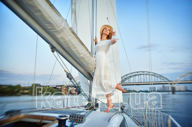 Красавица в белом платье и шляпке у мачты под парусом яхты Александра - katera.ua