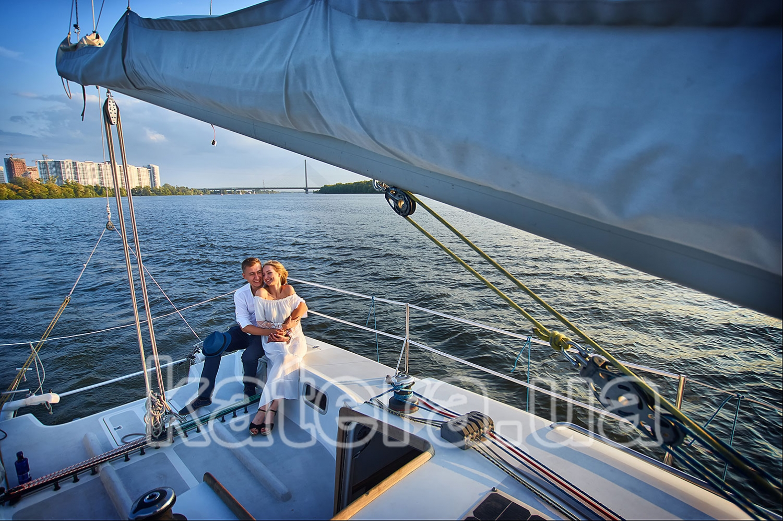 Милая молодая пара сидит на летней площадке яхты Александра нежно обняв друг друга - katera.ua