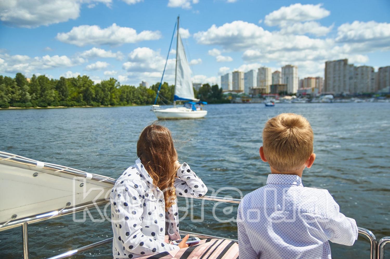 Дети наблюдают на носу катамарана за проходящей мимо парусной яхтой - katera.ua