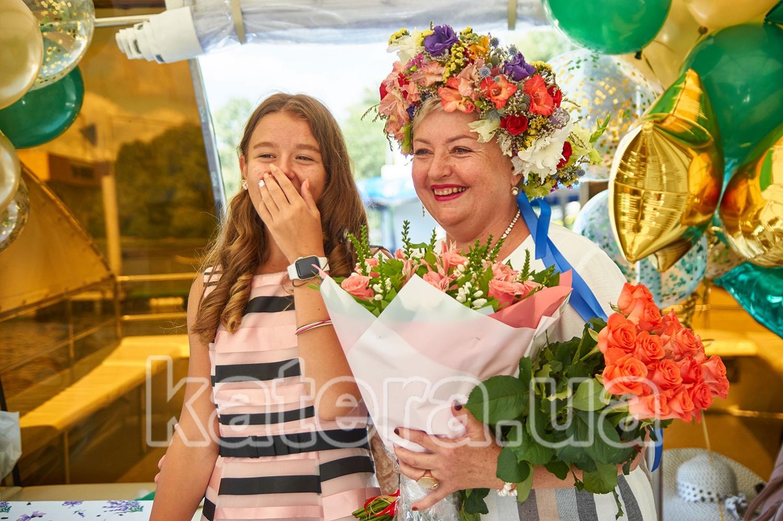 Именинница с красивыми букетами цветов принимает поздравление от гостей - katera.ua