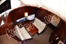 Стол и диваны напротив кухни на яхте Фридом - Katera.ua