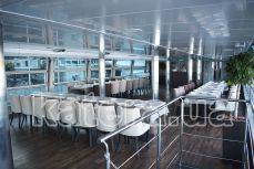 Вид салона на нижней палубе со столами и стульями на теплоходе Silver Wave - Katera.ua